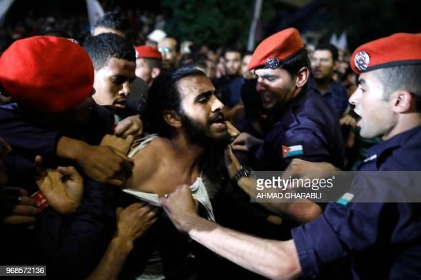 Jordanian policemen try to detain a demonstrator during a protest near the prime minister's office in Amman Jordan on June 6 2018 Jordanian Prime...
