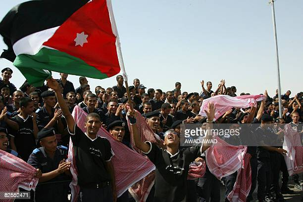 Jordanian policemen wave a national flag and their chequered 'keffiye' headdresses at the end of their training session at an academy in the town of...