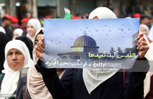 A Jordanian protester holds a banner reading in Arabic 'How can we return Jerusalem if we are not soldiers' during a demonstration against the US...