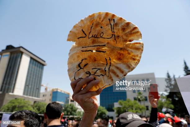 A Jordanian protester holds a loaf of bread with a slogan in arabic reading corruption = hunger during an antiausterity rally on June 6 in front of...