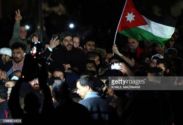 Jordanian protesters facing riot police chant slogans during a demonstration against the government's decision to raise taxes in the capital Amman on...