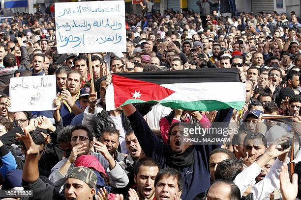 Jordanian protesters hold signs reading 'Until when poverty unemployment corruption and inflation Have mercy on us' and 'University student for sale'...