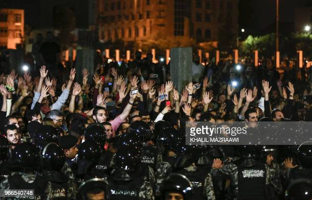 TOPSHOT Jordanian protesters raise their hands in before members of the gendarmerie and security forces during a demonstration outside the Prime...