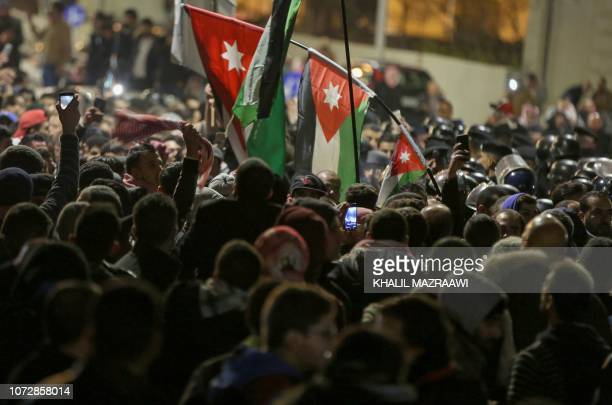 Jordanian protesters wave their national flag as they are confronted by riot police in the capital Amman on December 13 during a demonstration...