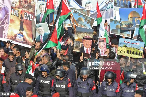 Jordanian protesters wave their national flags along with pictures of King Abdullah II and the Dome of the Rock and Aqsa mosque in Jerusalem during a...