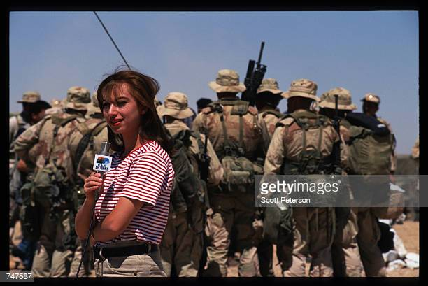 Jordanian reporter stands behind a group of US Marines from the 15th Expeditionary Forces May 31 1997 in Qatraneh Jordan The forces are taking part...
