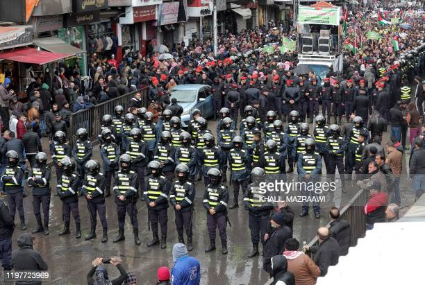 Jordanian security forces stand guard during a demonstration organised in Amman against the USbrokered proposal for a settlement of the Middle East...