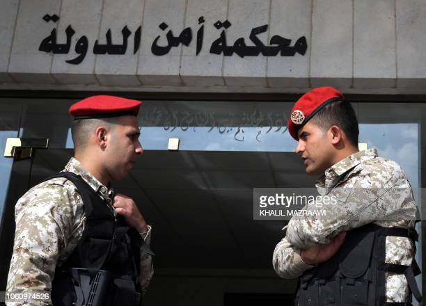 Jordanian security forces stand guard outside a military court as members of a cell accused of involvement in a shooting attack in 2016 go on trial...