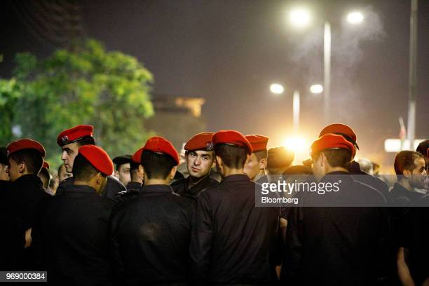 Jordanian security forces wait for the call to prayer to end ahead of a demonstration to protest a draft income tax law near the prime minister's...
