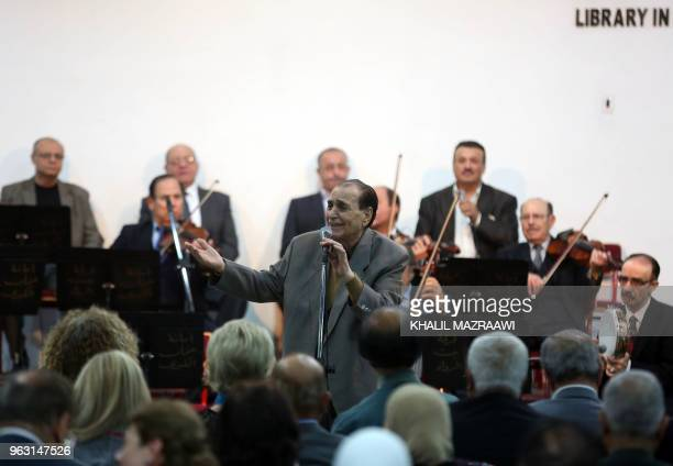 Jordanian singer Mohamed Wahib sings with the Beit alRowwad ensemble during a concert at Hussein Cultural Center in Amman on March 13 2018 Beit...