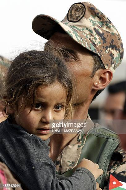 A Jordanian soldier carries a young Syrian refugee at the alRoqban makeshift camp on the border with Syria before driving a group of refugees to the...