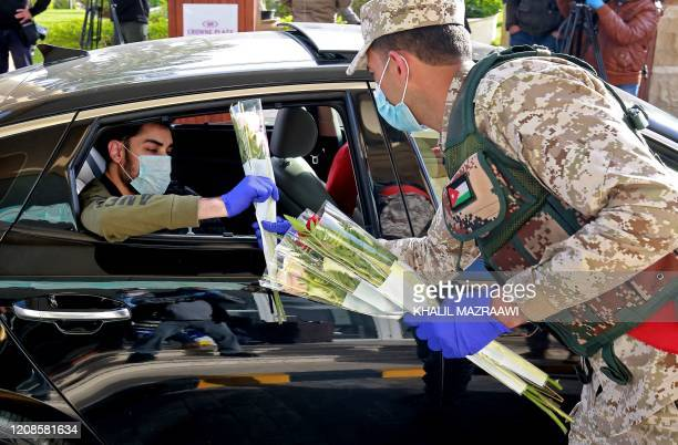 A Jordanian soldier greets people with flowers as they leave a Dead Sea resort where they have been quarantined for 14 days approximately 60...