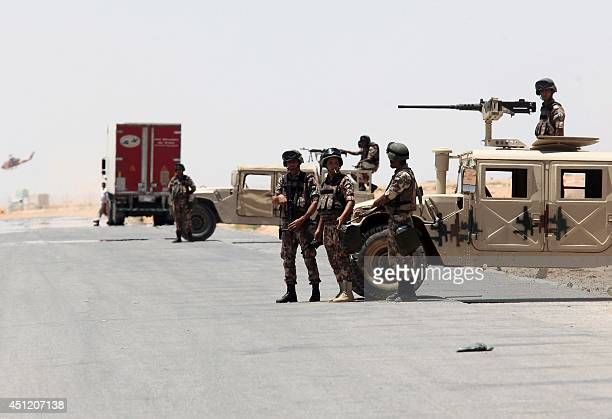 Jordanian soldiers stand guard near their military vehicles at the AlKarameh border point with Iraq on June 25 2014 as Jordan reinforced its border...