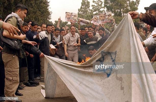 Jordanian students set a homemade Israeli flag on fire at Jordan University in Amman during a demonstration 18 April 2004 against the killing of...