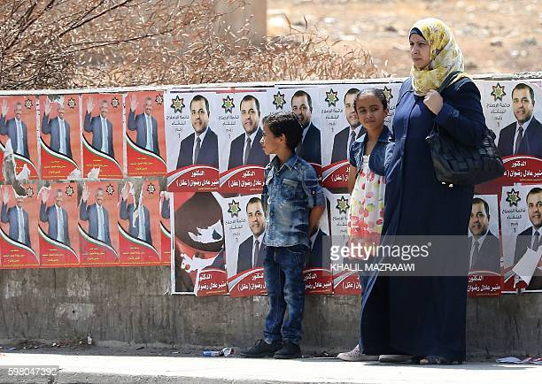 A Jordanian woman and her children stand in front of campaign posters on August 31 2016 in the Palestinian refugee camp of Baqaa north of Amman ahead...