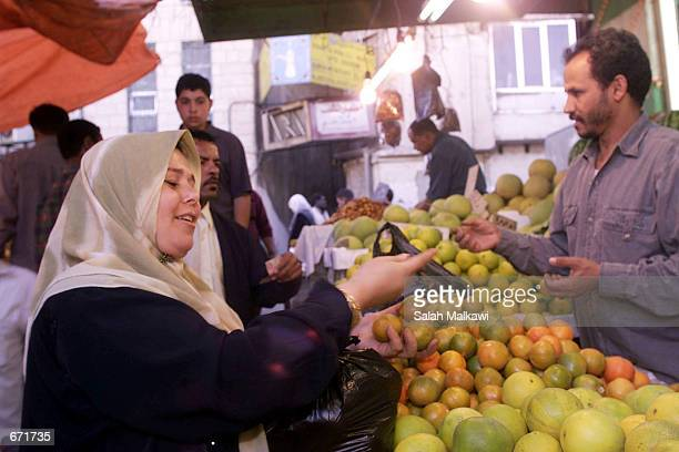 Jordanian woman checks vegetables at a wholesale market in Amman on November 15 before the start of the Holy Islamic month of Ramadan Muslims all...