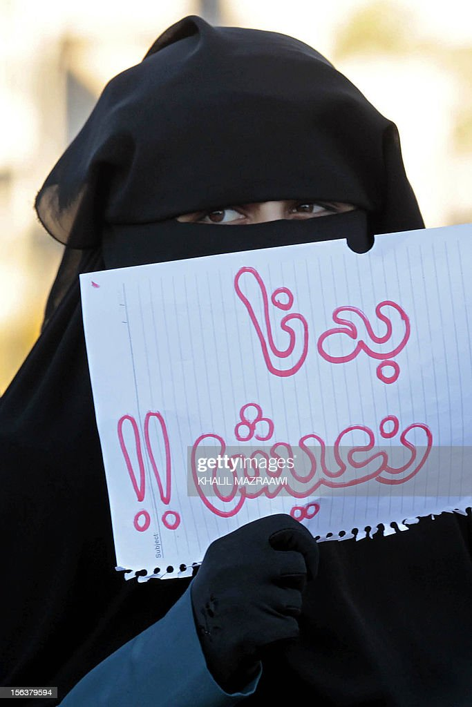 A Jordanian woman holds a sign in Arabic reading 'We want to live' as protesters block a main road during a demonstration against a rise in fuel prices in downtown Amman on November 14, 2012. Jordan was hit by a wave of protests and strikes while rioting broke in southern cities and a police station was attacked, security officials said, as anger mounted against a whopping rise in fuel prices.