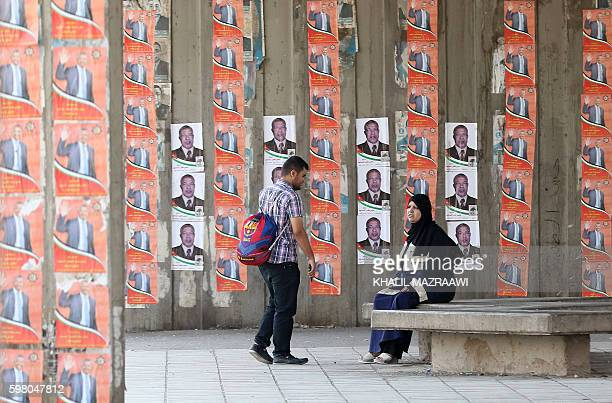 A Jordanian woman sits on a bench next to campaign poster on August 31 2016 in the Palestinian refugee camp of Baqaa north of Amman ahead of the...