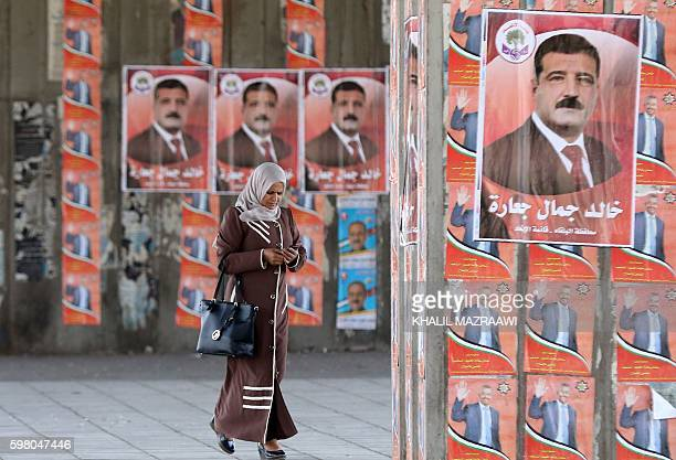 A Jordanian woman walks past a campaign poster of candidate Khaled alJaarah on August 31 2016 in the Palestinian refugee camp of Baqaa north of Amman...