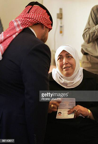 Jordanian woman who lost her daughter in one of the hotel's bombings shows her picture to King Abdullah II at a Jordan hospital 11 November 2005...