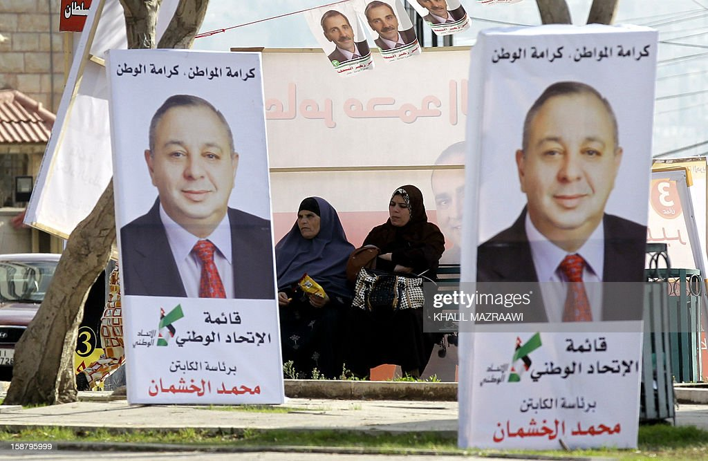 Jordanian women sit near pictures of parliament candidates in Amman on December 29, 2012. Jordan's electoral authority set January 23 as the date for a general election after King Abdullah II dissolved parliament despite a boycott pledge by the opposition Muslim Brotherhood.