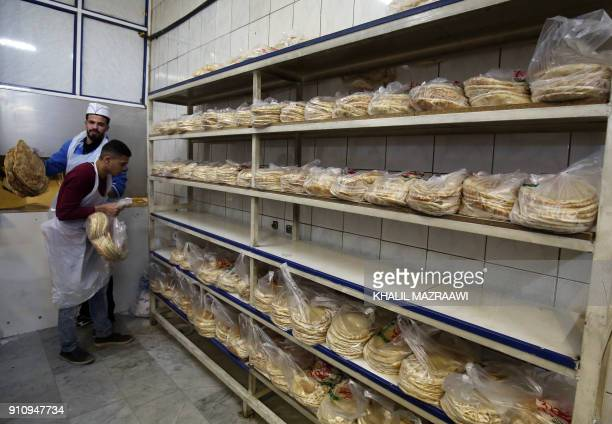 Jordanian workers bake bread at a bakery in the Jordanian capital Amman on January 27 2018 Jordan's Minister of Industry announced the decision to...