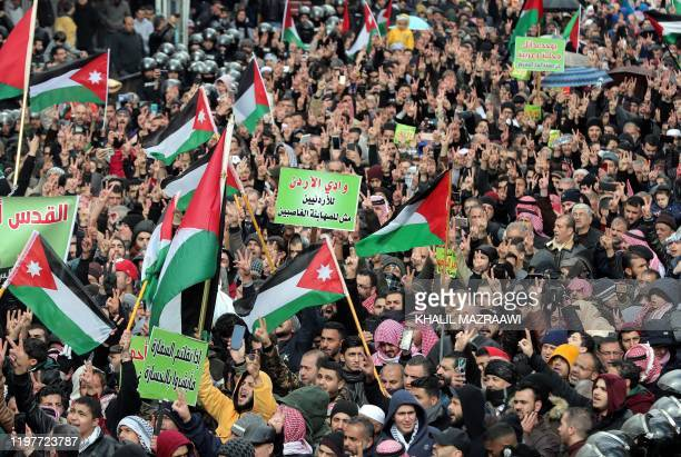 Jordanians and Palestinians waving national and Palestinian flags take to the streets of Amman, in front of al-Husseini mosque in the centre of the...