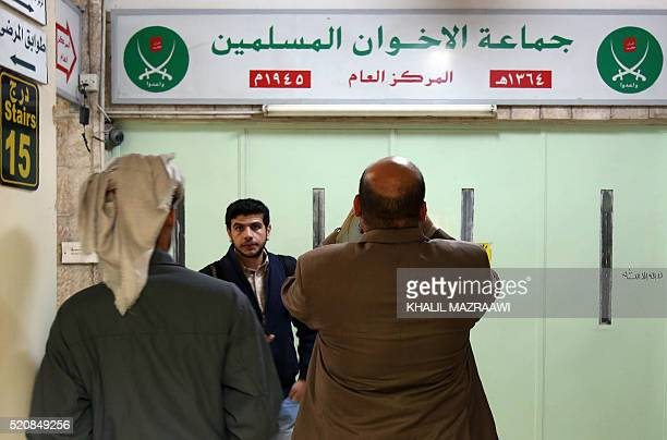 Jordanians check the main entrance of the Muslim Brotherhood's office in the Jordanian capital, which was sealed with wax after it was shut by police...