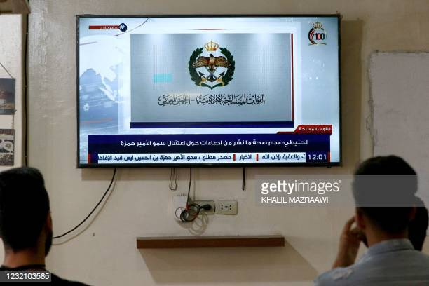Jordanians follow the latest political developments in their country on a television set at a cafe in the capital Amman, on April 4, 2021. - Jordan's...