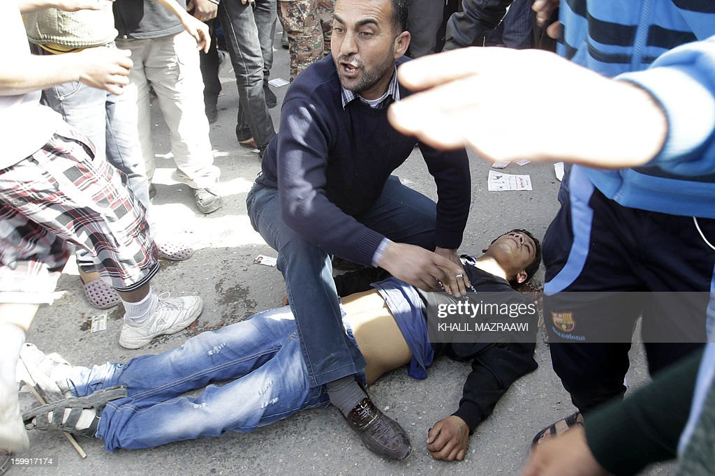 Jordanians help a friend after he was wounded in a fight between candidate supporters outside a polling station in the Palestinian refugee camp of Baqaa, north of Amman, on January 23, 2013. Jordanians are voting in a parliamentary poll snubbed by Islamists who have staged strident pro-reform protests and who have already slammed what is expected to be an opposition-free body as illegitimate.