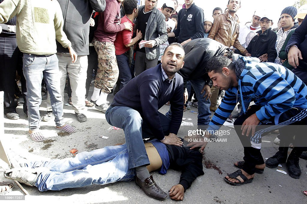Jordanians help a friend after he was wounded in a fight between supporters of rival candidates outside a polling station in the Palestinian refugee camp of Baqaa, north of Amman, on January 23, 2013. Jordanians are voting in a parliamentary poll snubbed by Islamists who have staged strident pro-reform protests and who have already slammed what is expected to be an opposition-free body as illegitimate.