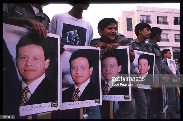Jordanians line the streets holding photographs of King Abdallah II June 8 1999 in Amman Jordan Four months after his accession to the throne the...