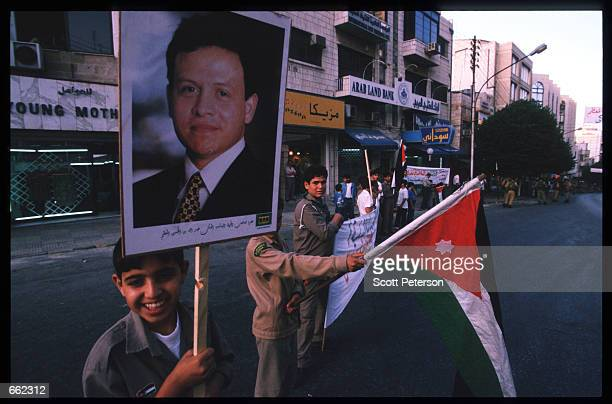 Jordanians line the streets holding up a photograph of King Abdallah II June 8 1999 in Amman Jordan Four months after his accession to the throne the...