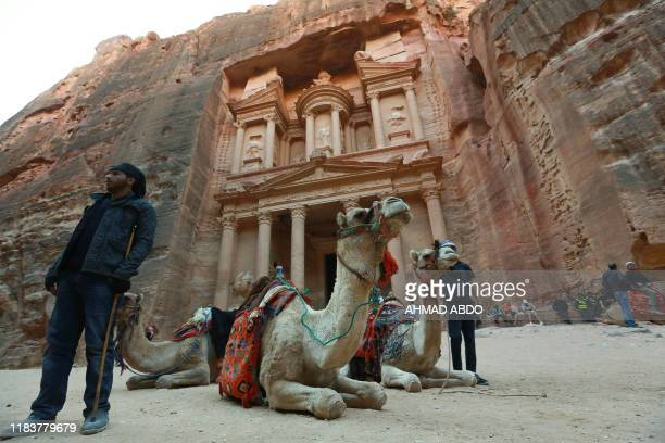 TOPSHOT Jordanians offer camel rides for tourists in front of the ancient Khaznah monument carved in the rock cliff in the archaeological city of...