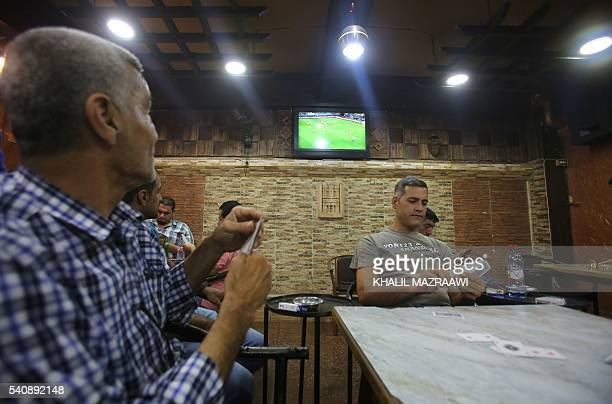 Jordanians play cards as they watch the EURO 2016 Group C football match between Germany and Ukraine at a café in Amman on June 12 2016 From Dubai to...