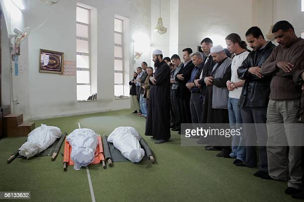 Jordanians pray during the funeral of three victims of last night's triple bombing attacks on hotels in the Jordanian capital before their funeral...