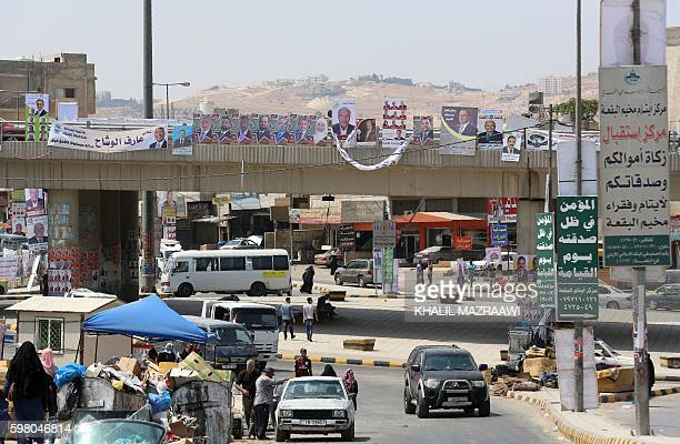 Jordanians walk on a street in the Palestinian refugee camp of Baqaa north of Amman on August 31 2016 as campaign posters are displayed ahead of the...