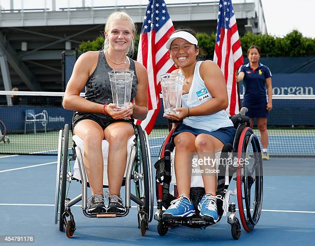 Jordanne Whiley of Great Britain and Yui Kamiji of Japan celebrate with their trophies after defeating Jiske Griffioen of the Netherlands and Aniek...