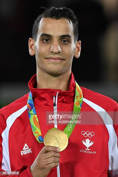 Jordan's Ahmad Abughaush poses with his gold medal on the podium after the men's taekwondo event in the -68kg category as part of the Rio 2016...