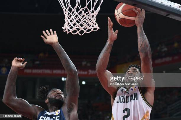 TOPSHOT Jordan's Dar Tucker takes a shot next to France's Mathias Lessort during the Basketball World Cup Group G game between Jordan and France in...