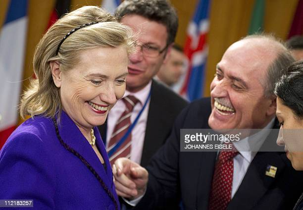Jordan's Foreign Minister Nasser Judeh jokes with US Secretary of State Hillary Clinton before the ISAF working lunch as part of the twodaylong NATO...
