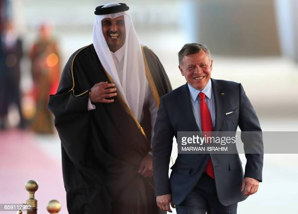 CORRECTION Jordan's King Abdullah II and Qatar's Emir Sheikh Tamim bin Hamad alThani smile as they attend a welcome ceremony at the Queen Alia...
