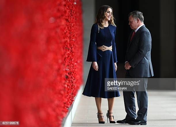 Jordan's King Abdullah II and Queen Rania talk after placing poppies at the Roll of Honour during their visit to the Australian War Memorial in...