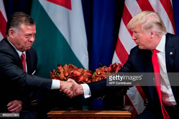 Jordan's King Abdullah II and US President Donald Trump shake hands before a meeting at the Palace Hotel during the 72nd United Nations General...