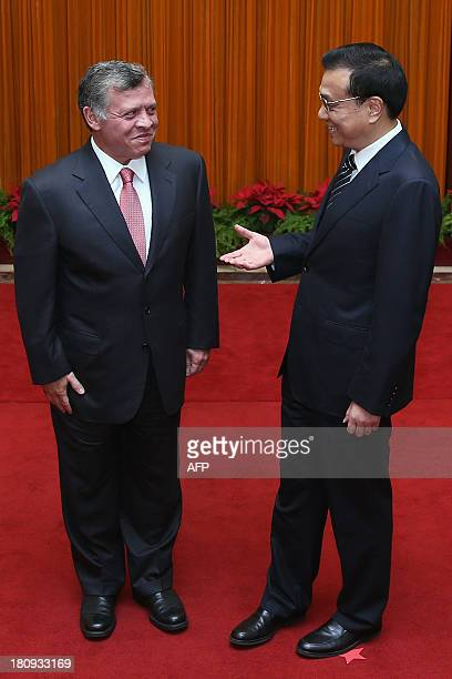 Jordan's King Abdullah II prepares to shake hands with Chinese Premier Li Keqiang at the Great Hall of People in Beijing on September 18, 2013. King...