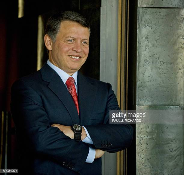 Jordan's King Abdullah II waits at the front door to greet US Democratic presidental candidate Barack Obama upon arrival at Beit AlUrdun the King's...