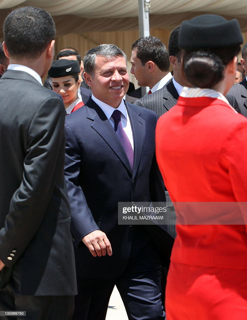 Jordan's King Abdullah II walks past flight attendants as he arrives to attend a ceremony to receive two new Airbus A330-200 acquired by state carrier Royal Jordanian at Queen Alia International Airport in Amman May 24, 2010. The ceremony was held as part of Independence Day celebrations.