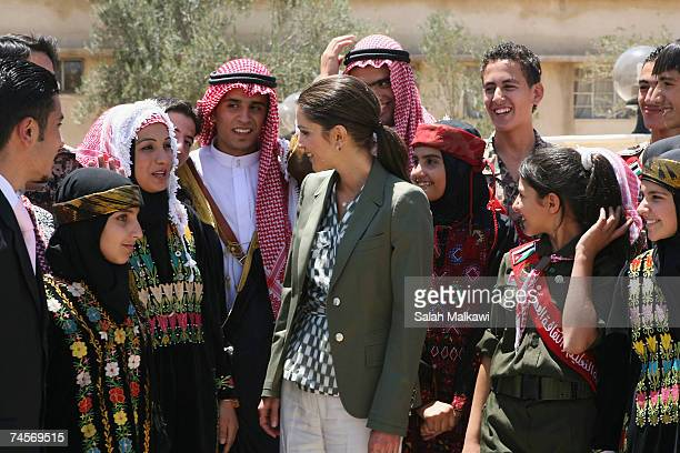 Jordan's Queen Rania poses with students as she arrives at the Queen Rania Society for Military Families on June 12 2007 in Zarqa Jordan