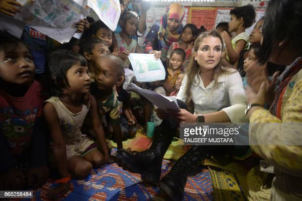 TOPSHOT Jordan's Queen Rania sits with Rohingya children inside a temporary school run by the United Nations Children's Fund during her visit to the...