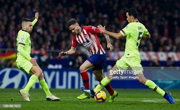 Jordi Alba and Sergio Busquets of FC Barcelona competes for the ball with Saul Niguez of Atletico de Madrid during the La Liga match between Club...